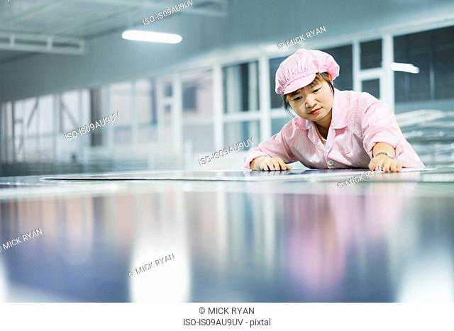 Female worker in solar panel assembly factory, Solar Valley, Dezhou, China
