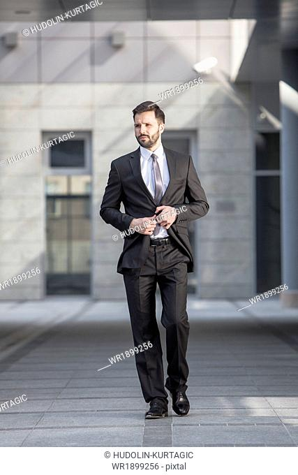 Businessman buttoning suit jacket outdoors