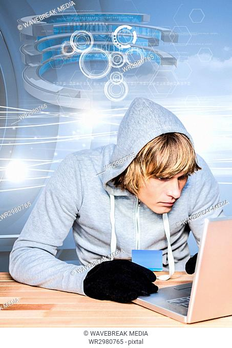 Hacker holding a credit card while using a laptop