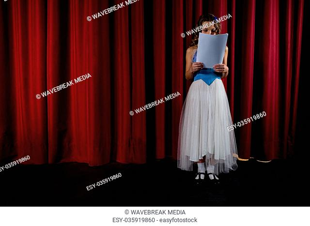 Female artist reading her scripts on stage