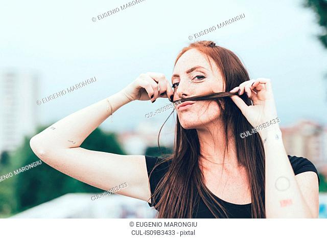 Portrait of young woman with freckles making mustache with long red hair