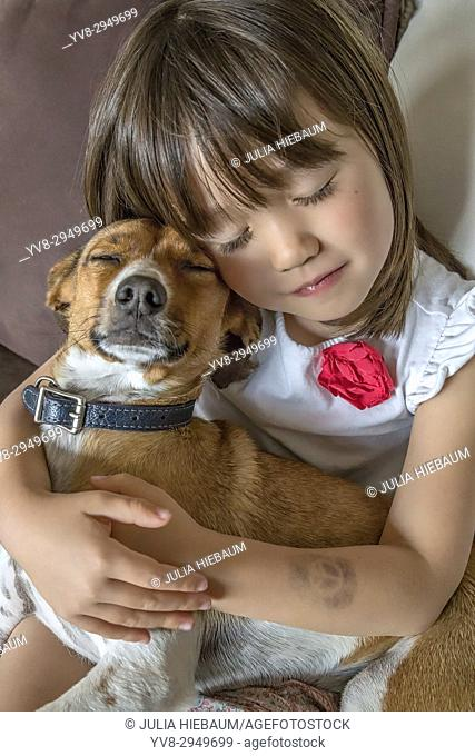A toddler girl and her pet with closed eyes