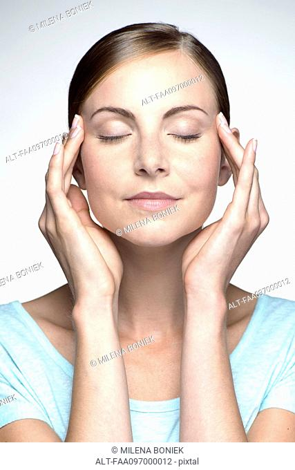 Young woman with headache holding head