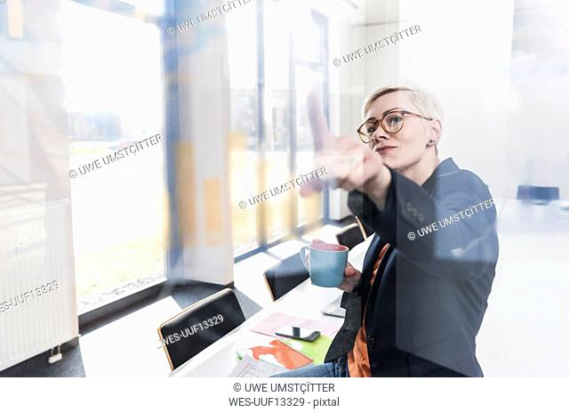 Confident businesswoman looking at glass pane in office