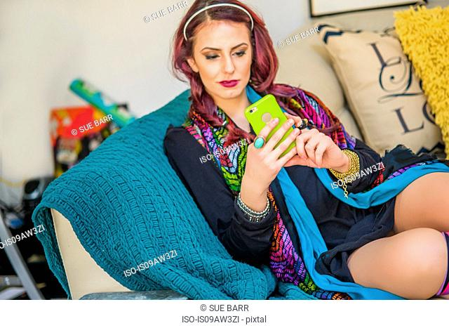 Young woman at home, sitting on sofa, using smartphone