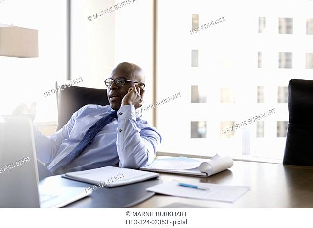 Lawyer talking on cell phone in conference room
