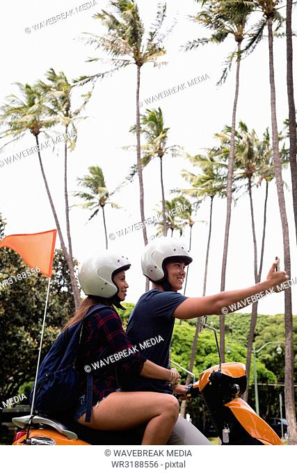Couple taking selfie with mobile phone while riding scooter