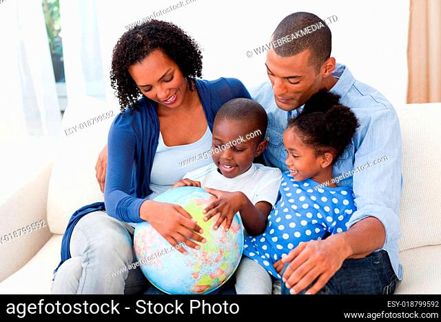 Happy family holding a terrestrial globe