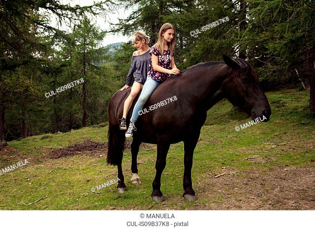 Girl and woman sitting bareback on horse in forest glade, Sattelbergalm, Tyrol, Austria