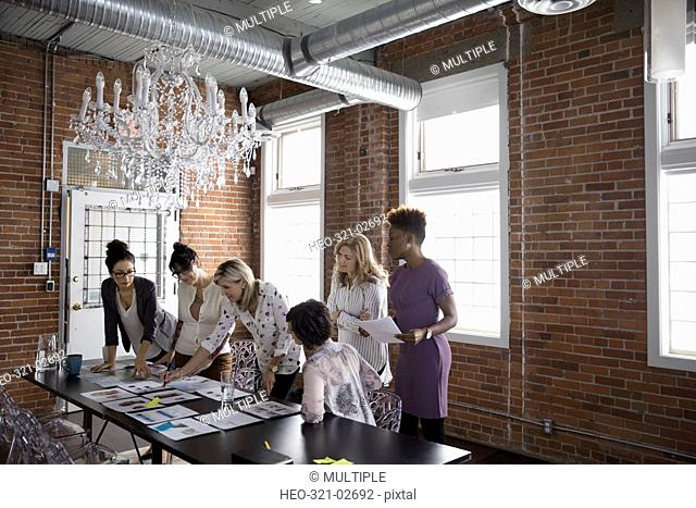 Female designers meeting and brainstorming reviewing proofs in conference room