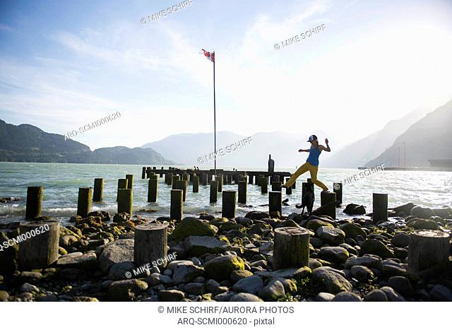 Side view of woman walking across pier ruins, Squamish, British Columbia, Canada