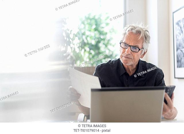 Senior man sitting in home office and using laptop