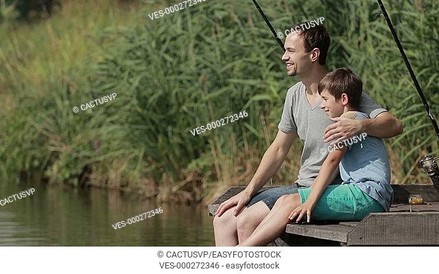 Smiling boy and his father fishing on pier