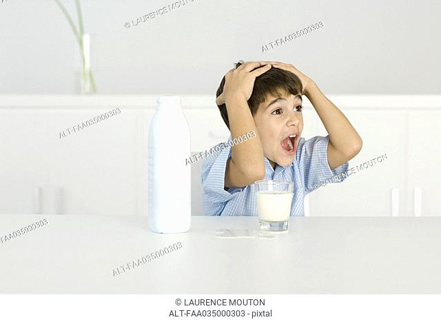 Boy with spilled milk, shouting, hands on head