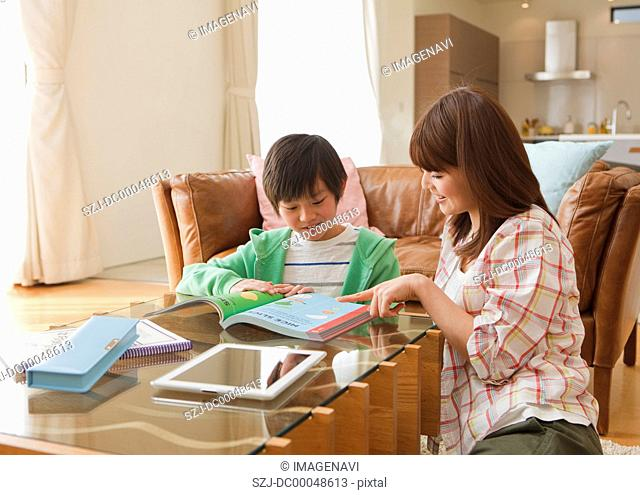 Mother and son studying in a living room