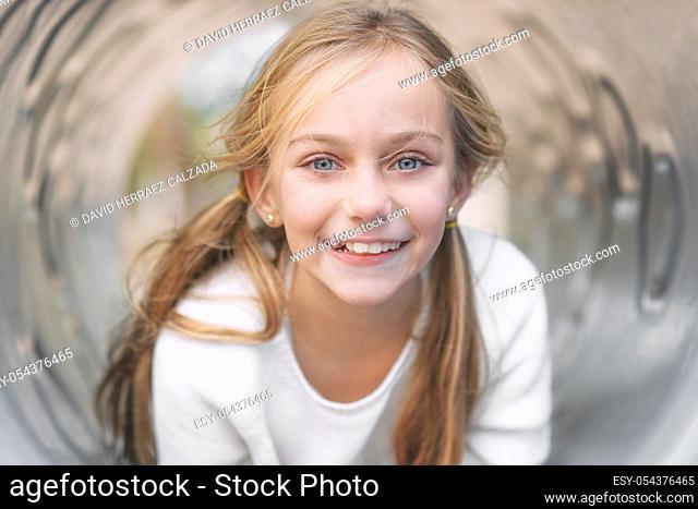 Pretty, little girl, having fun, lying on pipe on children playground