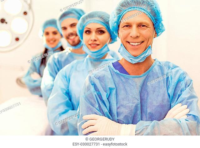 Beautiful doctors are looking at camera and smiling, standing in line in a modern operating room