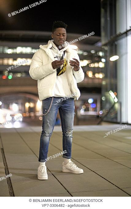 young stylish African man at night in city, looking at glasses in his hands, in Munich, Germany