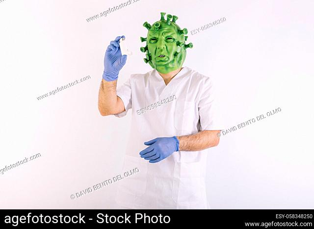 Person disguised as a coronavirus with a latex mask - covid-19 virus, wearing a doctor's suit, taking an asthma inhaler, on white background