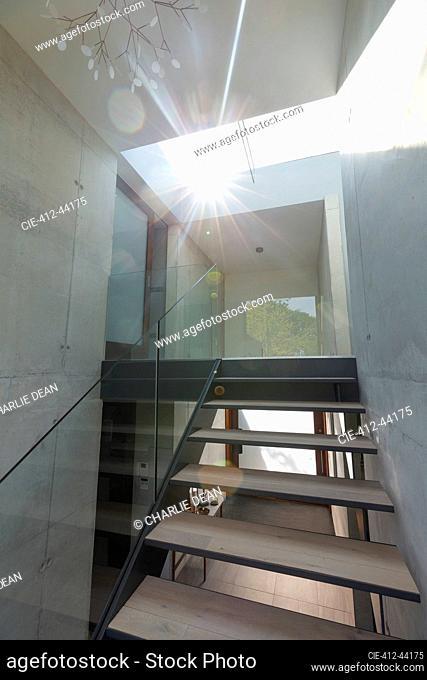 Sunlight shining through skylight over modern staircase in house