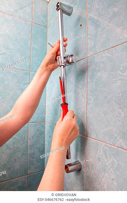 Replace broken wall mounted vertical height adjustable shower bar slider rail holder, close-up of hands remove the faulty slide rail