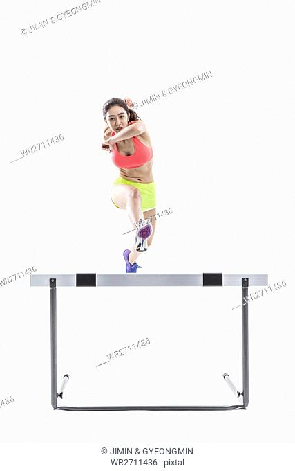 Dynamic female athlete jumping over obstacle