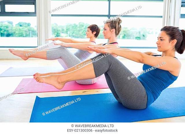 Women in boat pose in yoga class in fitness studio