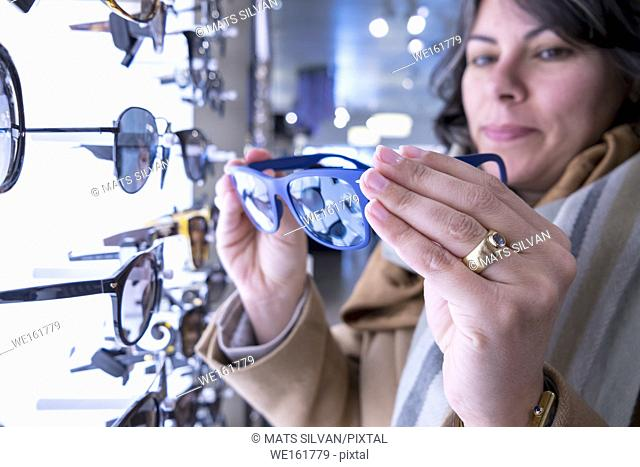 Woman Holding a Pair of Sunglasses in Retail Store