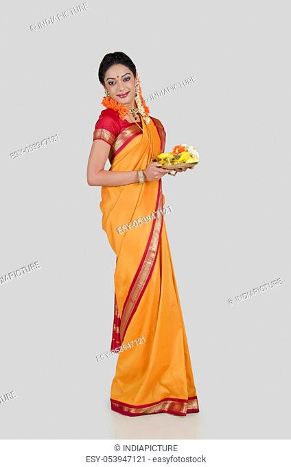 Portrait of a South Indian woman holding a thali