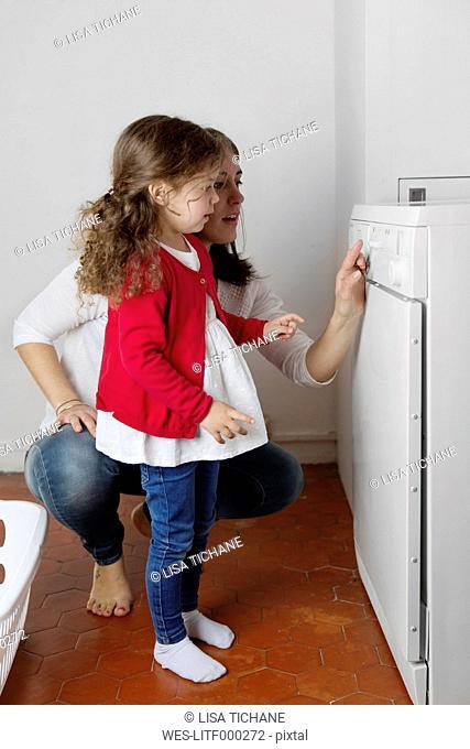 Mother explaining her little daughter operating of tumble dryer