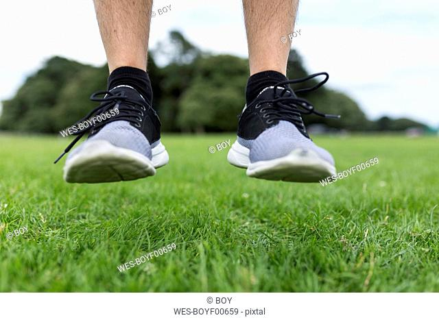 Shoes of athlete jumping on meadow