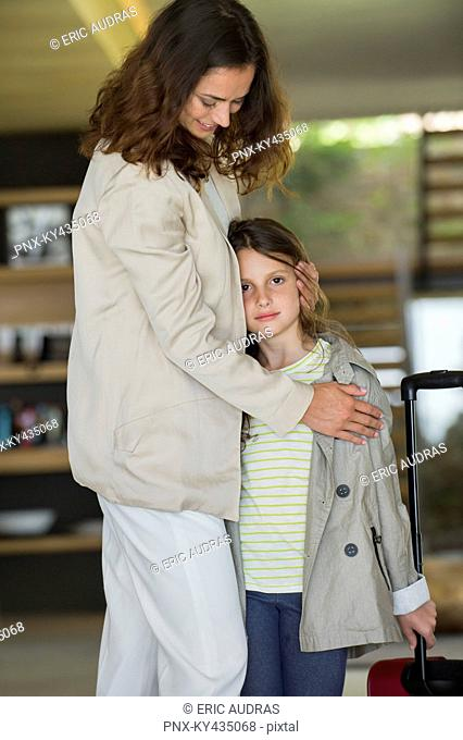 Smiling woman hugging her daughter