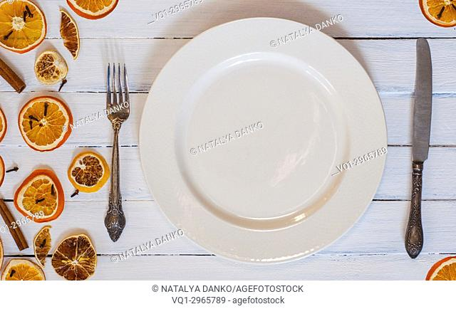 white empty dining plate with cutlery on a white wooden surface, top view