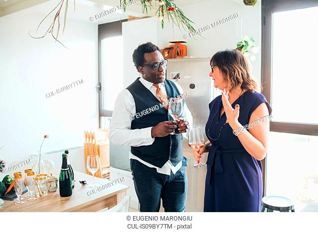 Businessman and businesswoman talking at party