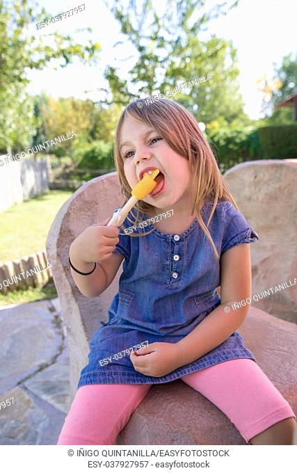four years old blonde girl with blue denim dress sitting in public park, biting orange or yellow ice lolly or popsicle