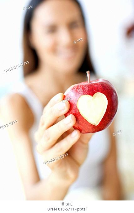 MODEL RELEASED. Young woman holding an apple with a heart shape