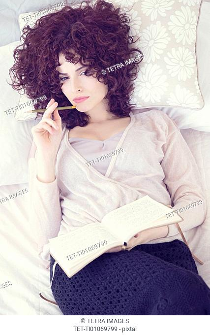 Portrait of beautiful brunette woman lying on bed with diary