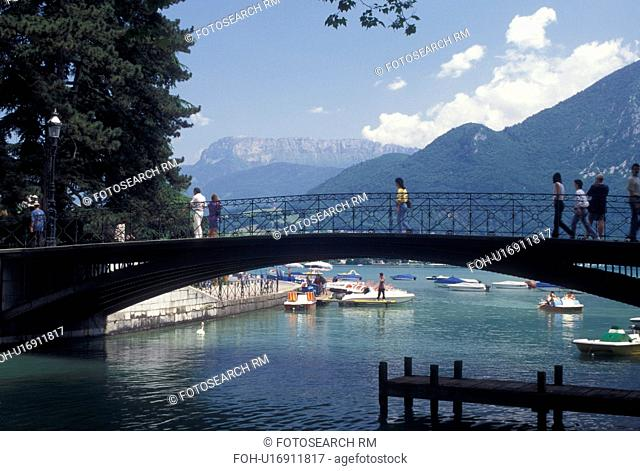 France, Annecy, Haute-Savoie, Rhone-Alpes, Europe, Pedestrian bridge crosses the Vasse canal on scenic Lake Annecy (Lac d' Annecy) surrounded by mountains in...