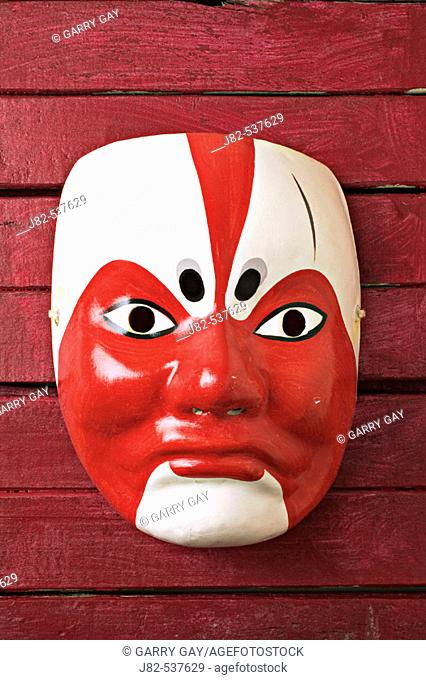 Asian mask on red wooden background