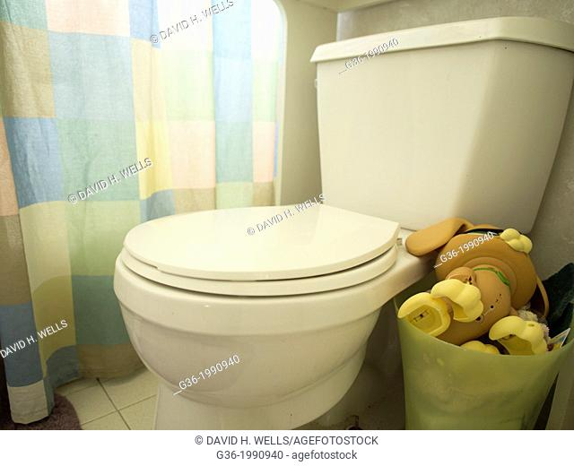 Toys in basket next to toilet inside a foreclosed home in Talahassee, Florida, United States