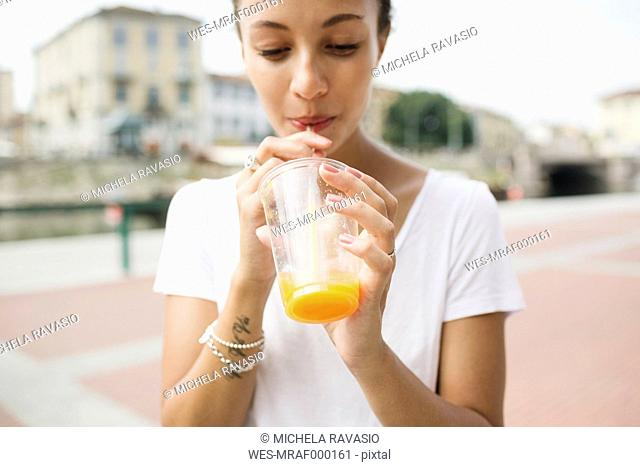 Young woman drinking an orange juice outdoors