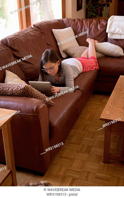 Girl using digital tablet in living room
