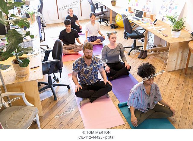 Serene creative business people meditating in office
