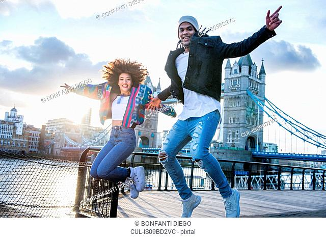 Young couple outdoors, jumping for joy, Tower Bridge in background, London, England, UK