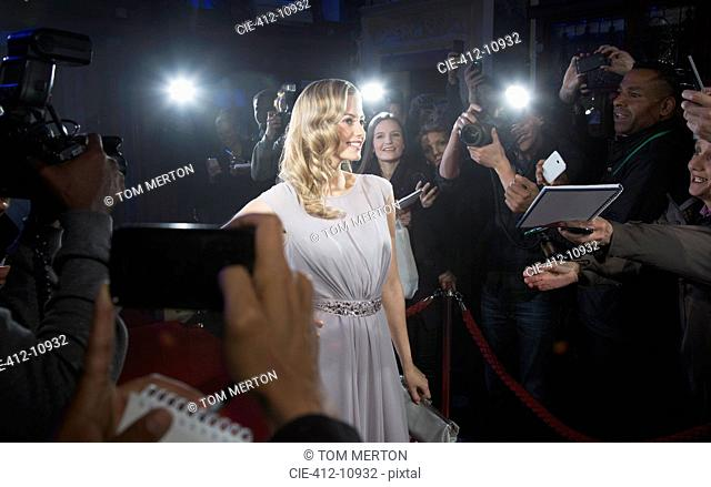 Female celebrity posing for paparazzi on red carpet