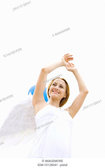 Young woman wearing angel wings, smiling, portrait