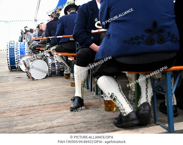 05 May 2019, Bavaria, Benediktbeuern: Musical instruments and beer mugs stand on the floor during the service of the patron saint's day of the Bavarian mountain...