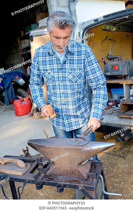 Farrier using anvil