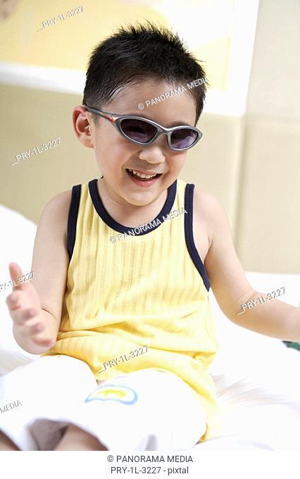 Boy wearing sunglasses smiling