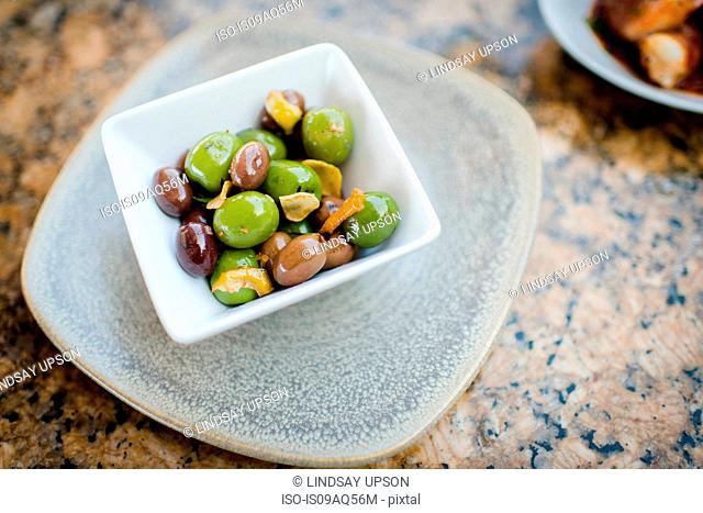 Bowl of black and green olives on restaurant table